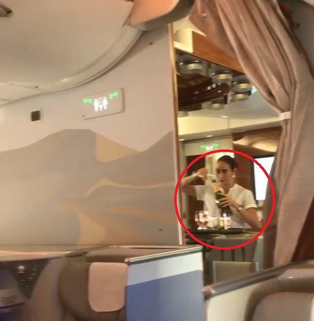 Stewardessa przelewa szampana z kieliszka do butelki