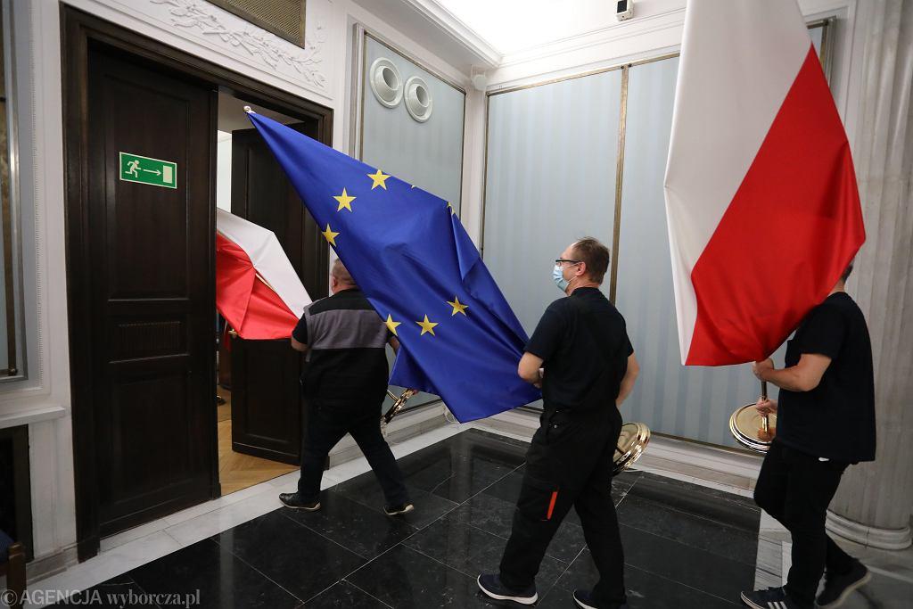 Projekt nowej ustawy o służbie zagranicznej błyskawicznie pozwoli na zatrudnianie ludzi zaraz po studiach, bez aplikacji w Akademii Dyplomatycznej MSZ. Do ambasad powchodzą politycy i ludzie bez przygotowania. Na zdjęciu: pracownicy sejmy wynoszą flagi polski i UE. Warszawa, 9 grudnia 2020
