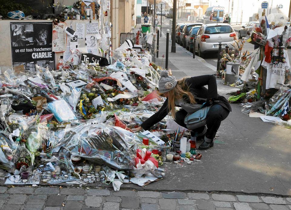 Paryż - miesiąc po zamachu na redakcję 'Charlie Hebdo' paryżanie składają kwiaty przed budynkiem, w którym zginęło 12 osób