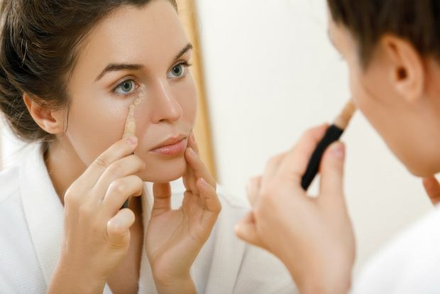 Woman using concealer for under eye circles