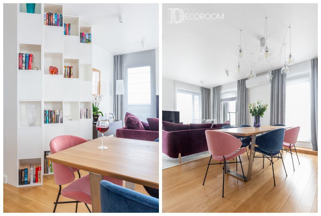 Ciekawe rozwiązania aranżacyjne w części dziennej mieszkania: biała zabudowa ustawiona pod kątem oraz kolorowe krzesła zestawione ze stołem w stylu industrialnym.