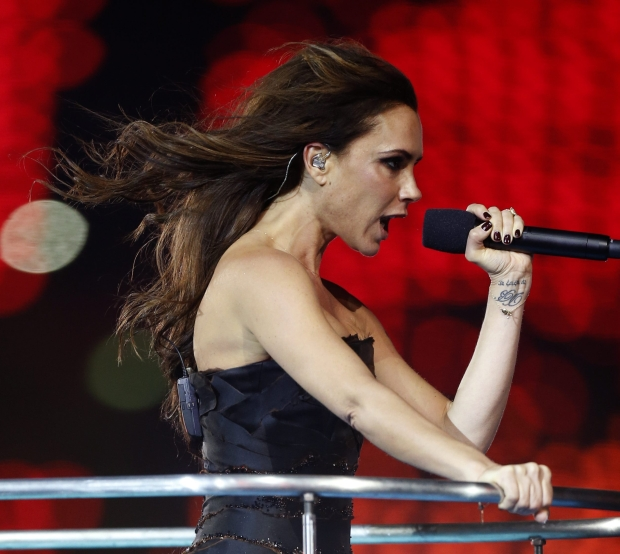 Victoria Beckham performs as Posh Spice with British band The Spice Girls during the Closing Ceremony at the 2012 Summer Olympics, Sunday, Aug. 12, 2012, in London. (AP Photo/Matt Dunham)