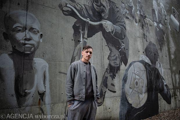 Bruno Althamer na tle muralu poświęconego Krzysztofowi Millerowi