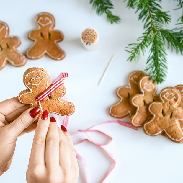 Ciasteczka imbirowe ludziki - delikatnie poszerzamy wykałaczką otwory i przeciskamy nią wstążkę