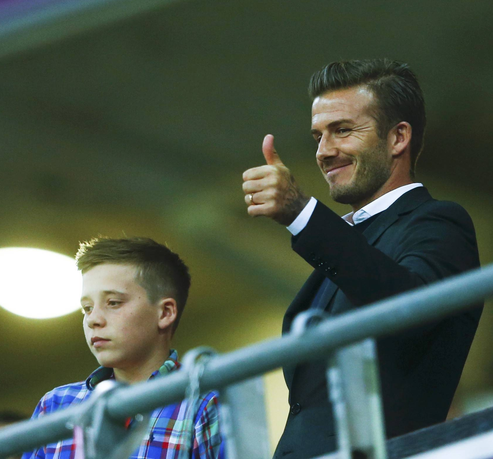 Soccer ace David Beckham (C) gives thumbs up as he stands with his son Brooklyn (L) and Britain's Prince William as they watch the men's preliminary first round Group A soccer match between Britain and UAE at the London 2012 Olympic Games in the Wembley Stadium in London July 29, 2012.               REUTERS/Eddie Keogh (BRITAIN  - Tags: ENTERTAINMENT OLYMPICS ROYALS SPORT SOCCER)