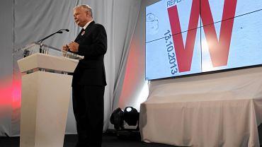 """Jarosław Kaczyński na konwencji w sprawie referendum. W tle kontrowersyjny plakat kampanii z literą """"W""""."""