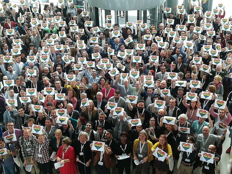 Zdjęcie aktywistów i aktywistek uczestniczących w konferencji ILGA  Europe w Warszawie stanowiące symboliczny wyraz wsparcia dla działaczy i działaczek LGBTI z Polski (osoby na zdjęciu trzymają w rękach kartki z tęczowym sercem i napisem 'civil' od civil society).