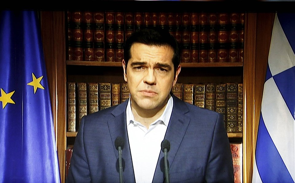 iGreek Prime Minister Alexis Tsipras is seen on a television monitor while addressing the nation in Athens