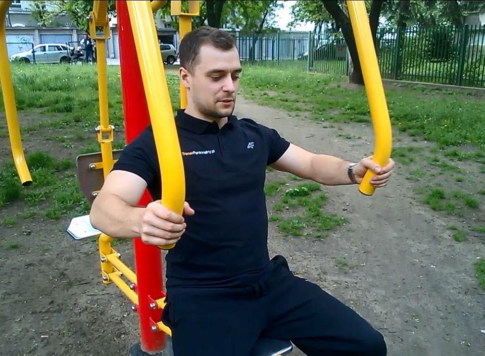 Instruktor kulturystyki Konrad Żuk pokazuje, jak ćwiczyć na siłowni plenerowej