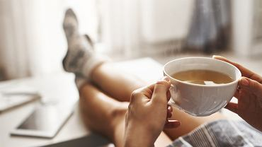 3Cup,Of,Tea,And,Chill.,Woman,Lying,On,Couch,,Holding