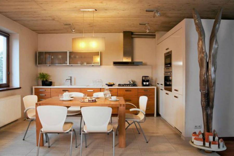 Kuchnia w bieli z drewnianymi elementami.