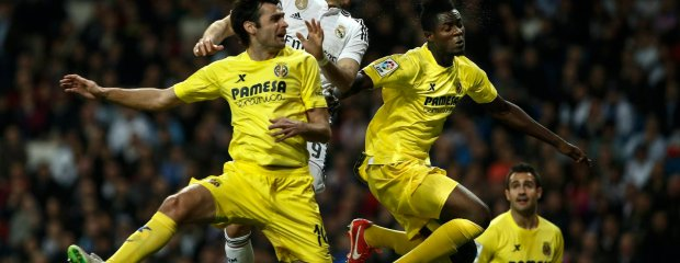 Real Madrid's Karim Benzema, centre, tries to score as he jumps with Villarreal's Chechu Dorado, left, and Villarreal's Eric Bailly, right, during a Spanish La Liga soccer match between Real Madrid and Villarreal at the Santiago Bernabeu stadium in Madrid, Spain, Sunday, March 1, 2015. (AP Photo/Andres Kudacki) SLOWA KLUCZOWE: XLALIGAX