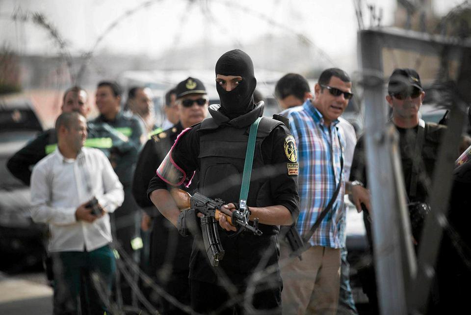 Zamaskowany funkcjonariusz policji - w tłumie demonstrantów - przed Akademią Policyjną - miejscem procesu.
