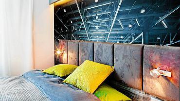 SYPIALNIA. Fototapeta, przedstawiająca surową stalową konstrukcję w opuszczonej hali fabrycznej, to po łóżku drugi element wystroju nawiązujący do klimatu loftowego. Kontrastem dla niej jest zagłówek z miękkich poduch obitych tkaniną przypominającą welur. Na podłodze ułożono dębowe deski, lekko pobielane. Pasuje do nich surowe drewno, z którego zrobiono łóżko. Gdy podstawa łóżka jest szersza od materaca, nie potrzeba już stolików nocnych. Niezbędne drobiazgi można postawić na brzegu mebla.