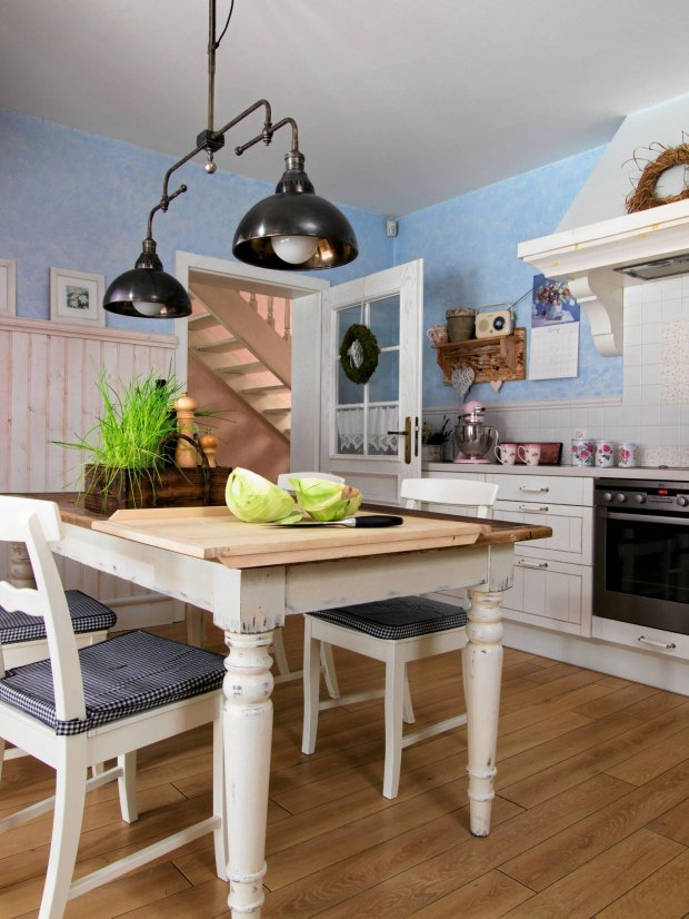 W kuchni panuje swojska, domowa atmosfera. Drewnianą obudowę okapu zrobił stolarz według projektu Agnieszki. Klimatu zasiedzenia dodaje wnętrzu stół zrobiony z?elementów mebli nienadających się już do użytku, a także pomalowana techniką przecierek ściana, wyglądająca jak stary mur. Na styl wnętrza duży wpływ mają również starannie dobrane dodatki: patynowana lampa, ludowe wianki, wiekowa skrzynka.