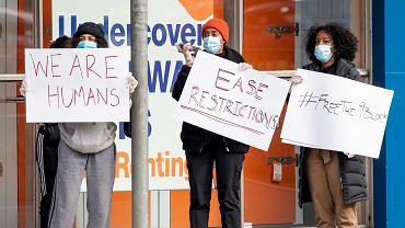 Mieszkańcy zamkniętego osiedla w Melbourne protestują przeciw narzuconym im ograniczeniom. Na kartkach można przeczytać: 'Jesteśmy ludźmi', 'Złagodźcie restrykcje', 'Uwolnijcie blok nr 9'