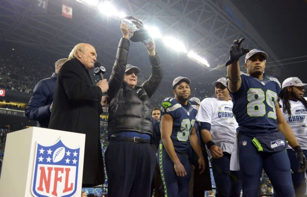Jan 19, 2014; Seattle, WA, USA; Seattle Seahawks owner Paul Allen hoists the George Halas Trophy after the 2013 NFC Championship football game against the San Francisco 49ers at CenturyLink Field. Mandatory Credit: Kirby Lee-USA TODAY Sports SLOWA KLUCZOWE: NPStrans TopPic