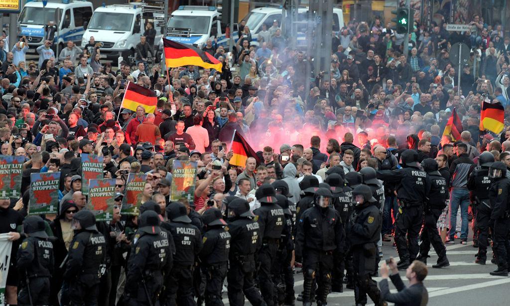 Demonstranci z bannerami 'Zatrzymać powódź azylantów' podczas zamieszek w Chemnitz, 28.08.2018 r.