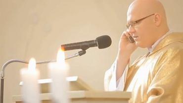 Ksiądz rozmawia przez telefon w trakcie ślubu