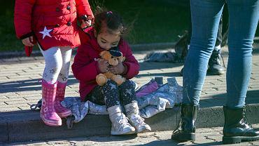 Grupa kilkunastu uchodźców i 8 dzieci z Syrii przed budynkiem Straży Granicznej w Michałowie