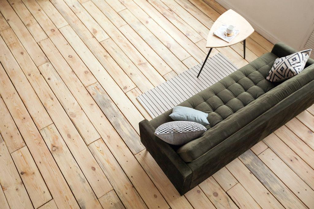 Zielona sofa na tle drewnianej podłogi prezentuje się pięknie.