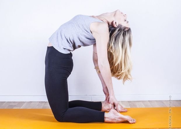 Joga: asana Ushtrasana. Uklęknij z kolanami na szerokość bioder. Dociśnij golenie i grzbiety stóp to podłogi. Połóż dłonie na biodrach i maksymalnie wydłuż kręgosłup. Unosząc jak najwyżej klatkę piersiową zacznij wyginać się do tyłu. Nie tracąc długości kręgosłupa przenieś ręce do tyłu i oprzyj na piętach. Odepchnij się od nich, aby jeszcze bardziej otworzyć klatkę piersiową. Głowę odchyl do tyłu nie napinając szyi. Po minucie odepchnij się od stóp i podnosząc najpierw mostek, podnieś się do pionu i usiądź na piętach.
