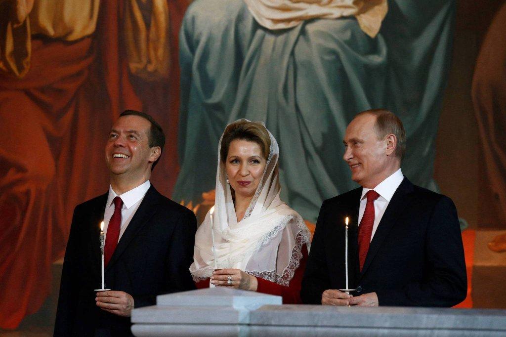 Dmitrij Miedwiediew z żoną Swietlaną i prezydent Władimir Putin w cerkwi w Moskwie