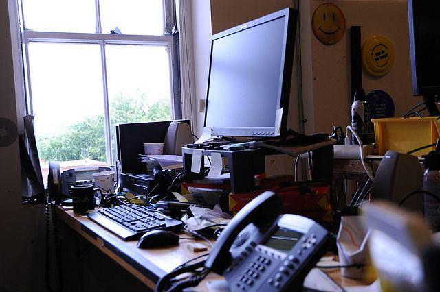 Tak wygląda stanowisko pracownika w siedzibie firmy Amazon w Seatle. Na zdjęciu biurko osoby pracującej w dziale Help Desk. Komputer, dwa telefony i wiele kubków z płynami oraz... kontrolowany bałagan. Zaletą stanowiska jest widok oraz okno, które da się otworzyć.