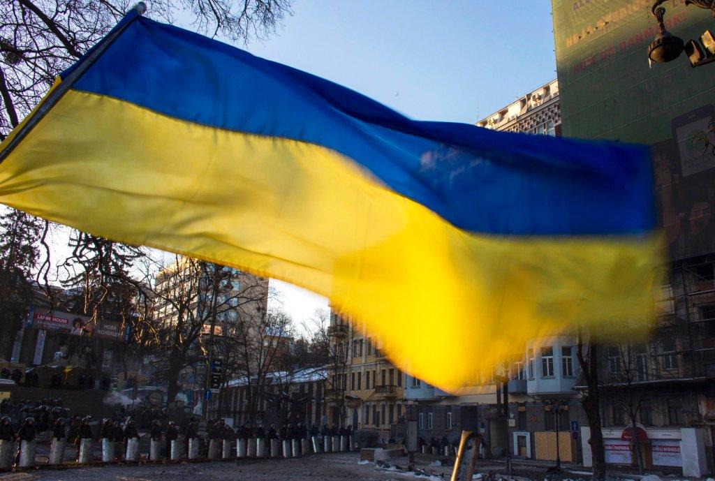 Ukraińska flaga na barykadzie Majdanu. W tle kordon milicji