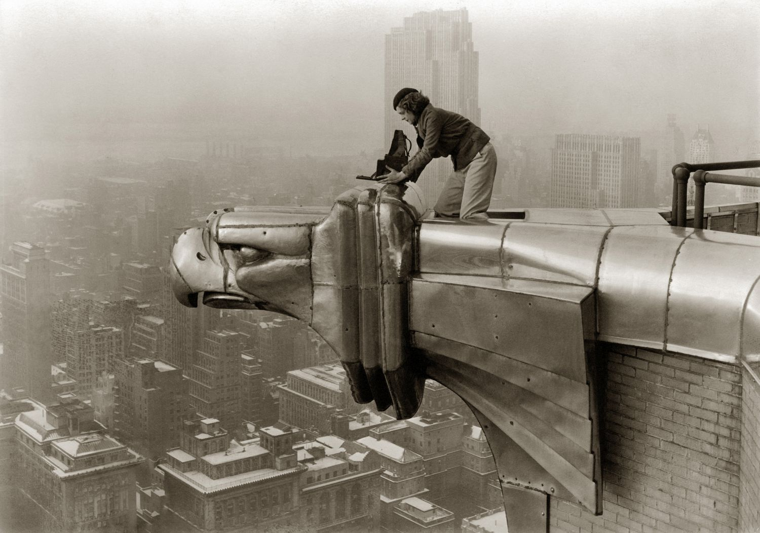 American photographer and journalist Margaret Bourke-White (1904 - 1971) perches on an eagle head gargoyle at the top of the Chrysler Building and focuses a camera, New York, New York, 1935. (Photo by Oscar Graubner/The LIFE Images Collection via Getty Images/Getty Images)