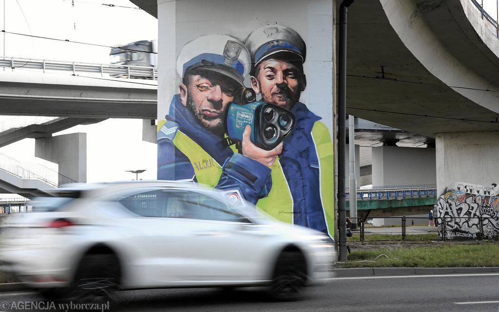 Mural z policjantami mierzącymi prędkość
