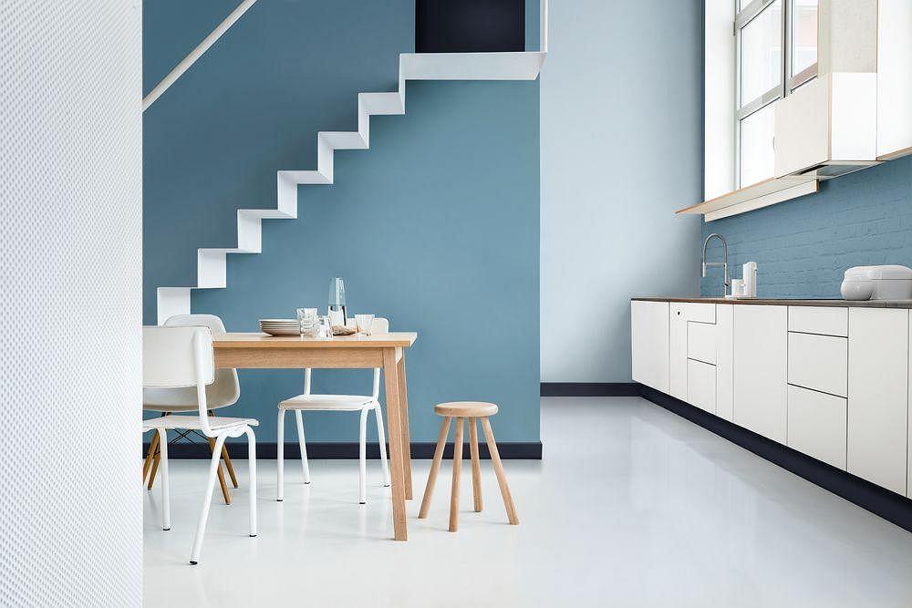 Niebieskie kolory ścian w kuchni świetnie łączą się z bielą mebli.
