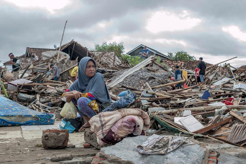Kobieta siedzi w miejscu gdzie kiedyś stał jej dom, Sumu, Indonezja, 24.12.2018