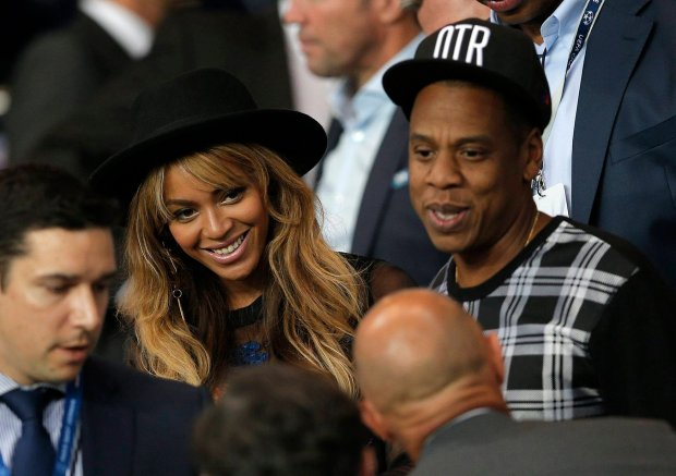 Jay Z and his wife Beyonce stand up at half time in the Champions League soccer match between PSG and Barcelona, at the Parc des Princes stadium, in Paris, Tuesday, Sept. 30, 2014. (AP Photo/Christophe Ena) SLOWA KLUCZOWE: xchampionsleaguex