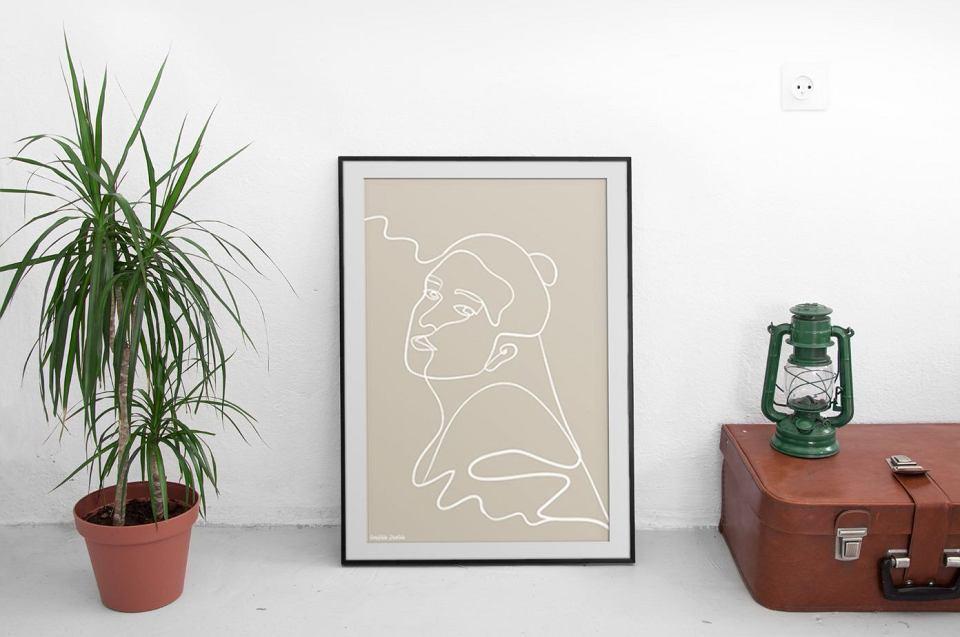 Beżowy plakat w ramie 'Spokój', z wizerunkiem kobiety.