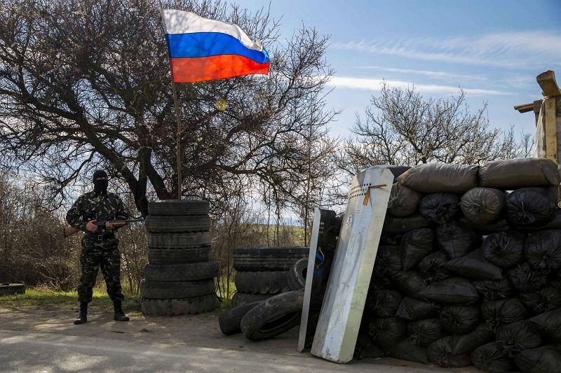 Jeden z uzbrojonych członków krymskiej samoobrony pod rosyjską flagą