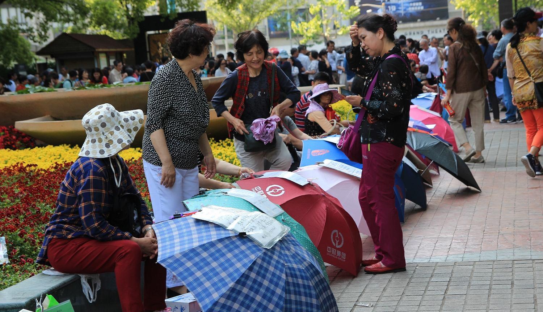 Rodzice szukają partnerów dla swoich dzieci na targu singli w Parku Ludowym w Szanghaju