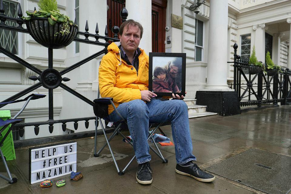 Richard Ratcliffe protestuje przed budynkiem irańskiej ambasady w Londynie. W dłoni trzyma zdjęcie więzionej w Iranie żony Nazanin z córką Gabriellą