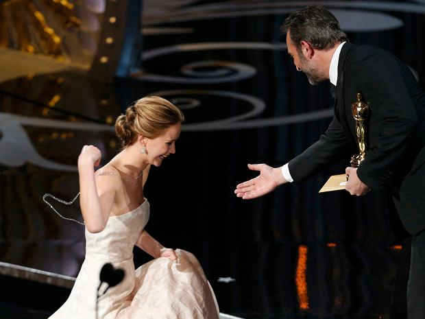 """Actress Jennifer Lawrence is helped by presenter French actor Jean Dujardin after she tripped walking up the stairs to accept the award for best actress for her role in """"Silver Linings Playbook"""" at the 85th Academy Awards in Hollywood, California February 24, 2013.      REUTERS/Mario Anzuoni (UNITED STATES  - Tags: ENTERTAINMENT)"""