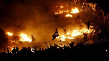 Protestujący w Kijowie stoją obok płonącej barykady