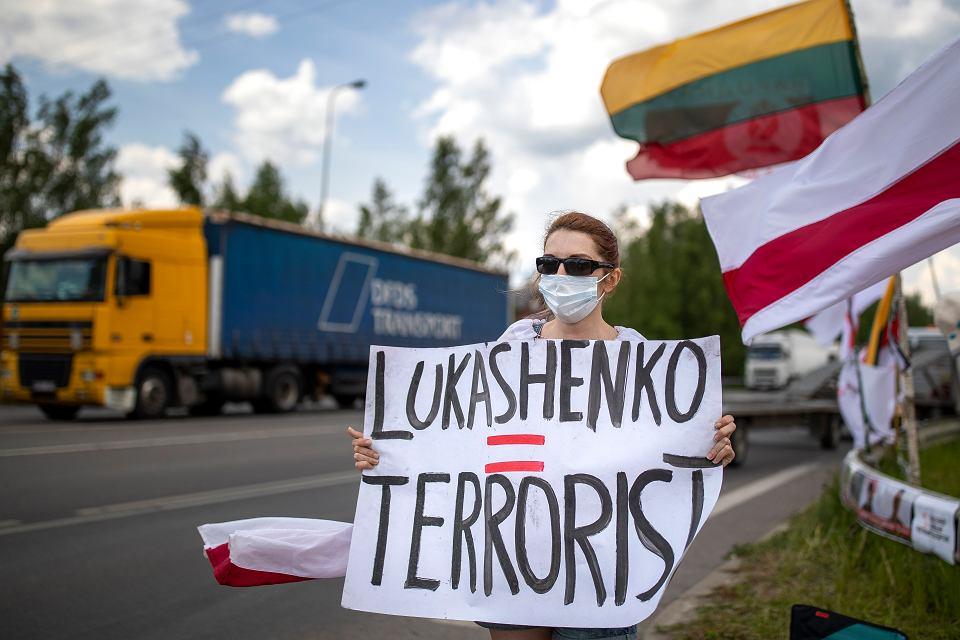 Kobieta trzyma transparent z napisem 'Łukaszenko - terrorysta' podczas protestu domagającego się wolności dla więźniów politycznych na Białorusi w pobliżu Miednik, litewsko-białoruskiego przejścia granicznego na wschód od Wilna, Litwa, 8 czerwca 2021 r.
