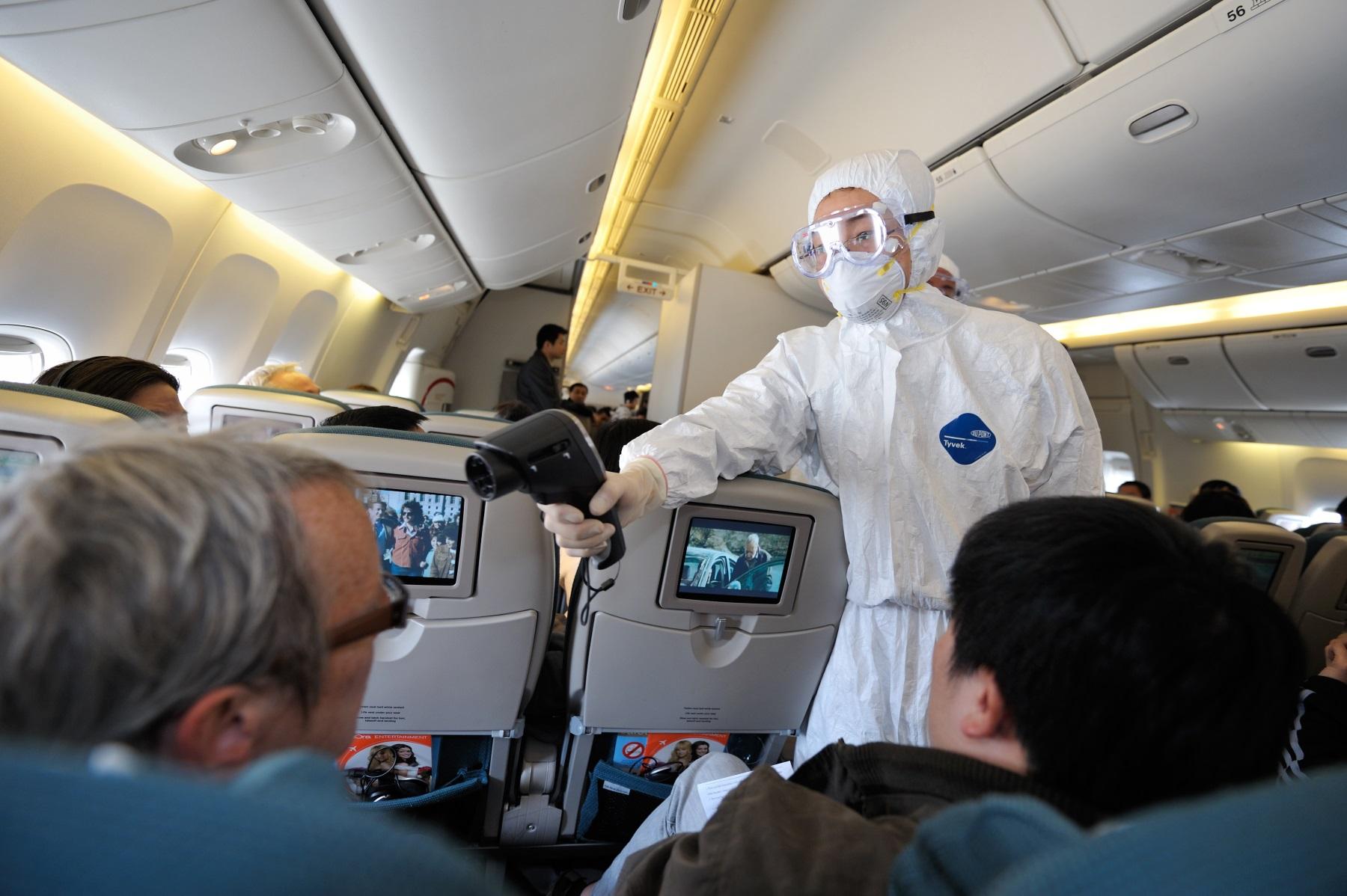 Personel pokładowy mierzy temperaturę ciała pasażerów termometrem bezdotykowym (fot: Shutterstock.com)