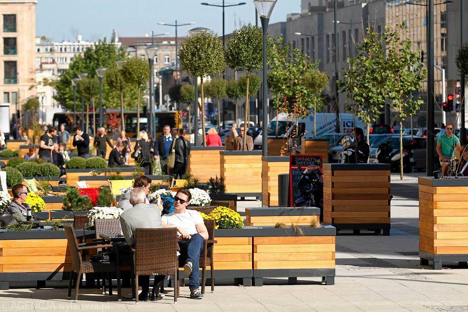 Ulica Świętokrzyska w Warszawie, październik 2014 r. Na wyremontowanej ulicy stanęły drewniane donice z drzewkami oraz miejskie meble.
