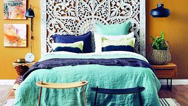 Główna ozdoba tej sypialni - efektowny zagłówek. Aby go odpowiednio wyeksponować, ścianę za nim pomalowano na kontrastowy kolor, który wydobył piękno ażurowego wzoru.