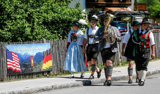 People wearing traditional Bavarian clothes walk on a street after a visit by U.S. President Barack Obama and German Chancellor Angela Merkel in Kruen, southern GermanyJune 7, 2015. Leaders from the Group of Seven (G7) industrial nations meet on Sunday in the Bavarian Alps for a summit overshadowed by Greece's debt crisis and ongoing violence in Ukraine.     REUTERS/Dominic Ebenbichler  SLOWA KLUCZOWE: :rel:d:bm:LR1EB671251TD