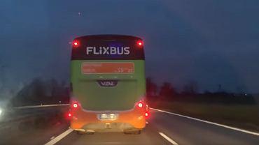 Kadr z nagrania, na którym widać jak kierujący autokarem blokuje przejazd karetce pogotowia ratunkowego
