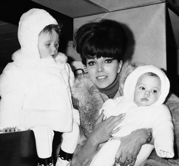 (Actress Joan Collins, wife of Anthony Newley, has her hands full at London Airport as she prepares to leave for Milan with her children, Tara, two years old, and Sacha, four months, Jan. 19, 1966. From Milan, Miss Collins will travel to St. Moritz for a winter vacation. (AP Photo/Victor Boynton)