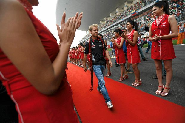 Grid girls clap as Red Bull Formula One driver Sebastian Vettel of Germany walks on a red carpet during the Indian F1 Grand Prix at the Buddh International Circuit in Greater Noida, on the outskirts of New Delhi, October 27, 2013. REUTERS/Ahmad Masood (INDIA  - Tags: SPORT MOTORSPORT F1)   SLOWA KLUCZOWE: :rel:d:bm:SR1E9AR0VDS2L