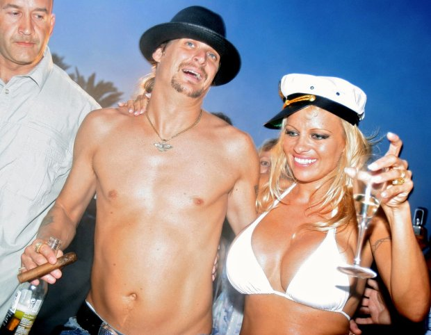 Canadian actress Pamela Anderson (R) shares a drink with her husband, US musician Kid Rock (C), the day of their wedding, on Pampelone's beach in Saint-Tropez, Southern France, 29 July 2006. Anderson, 39, married Rock, 35, aboard a yacht. AFP PHOTO ERIC ESTRADE