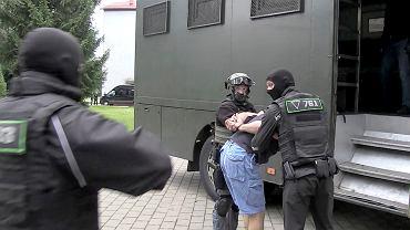 Funkcjonariusz KGB zatrzymuje osoby podejrzane o organizowanie ataków terrorystycznych na Białorusi w ramach kampanii prezydenckiej.